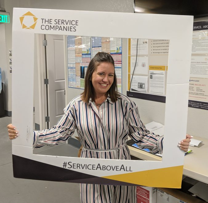 Stephanie Leger, Corporate Compliance Auditor posing with The Service Companies frame