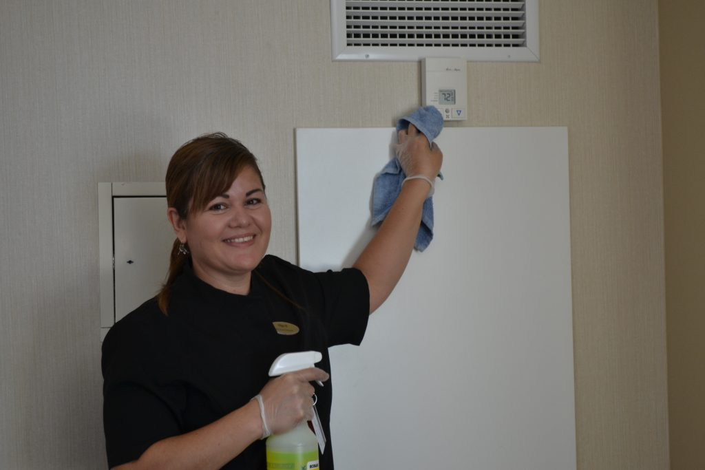 Smiling hotel cleaner using cleaning cloth to clean air conditioning unit