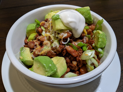 Beef chili with avocado and sour cream.