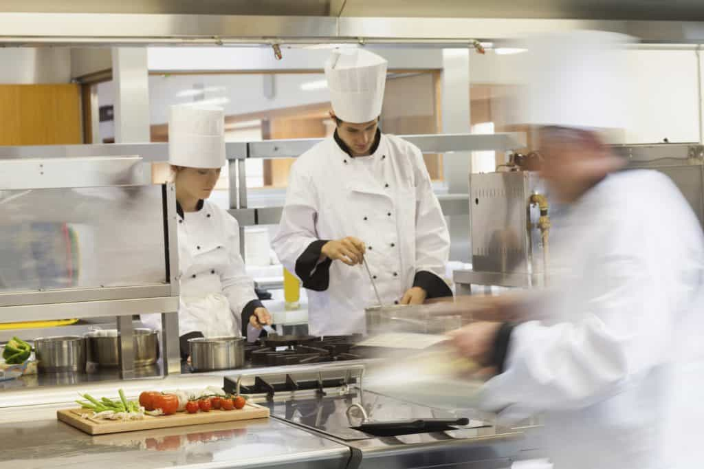 Multiple chefs moving and cooking in a kitchen