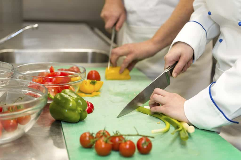 Two chefs cutting various vegetables