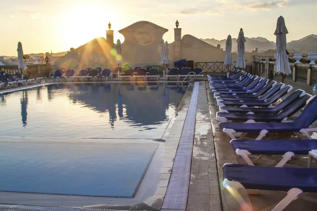 Rectangular pool surrounded by pool chairs at sunset