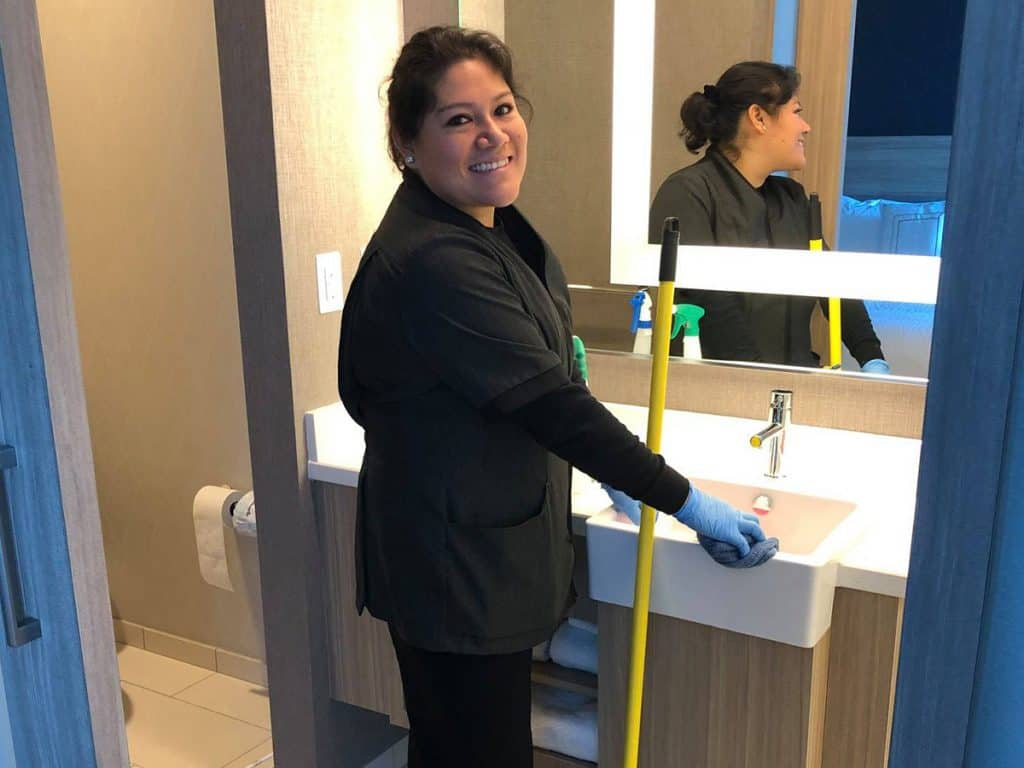 housekeeper cleaning a bathroom