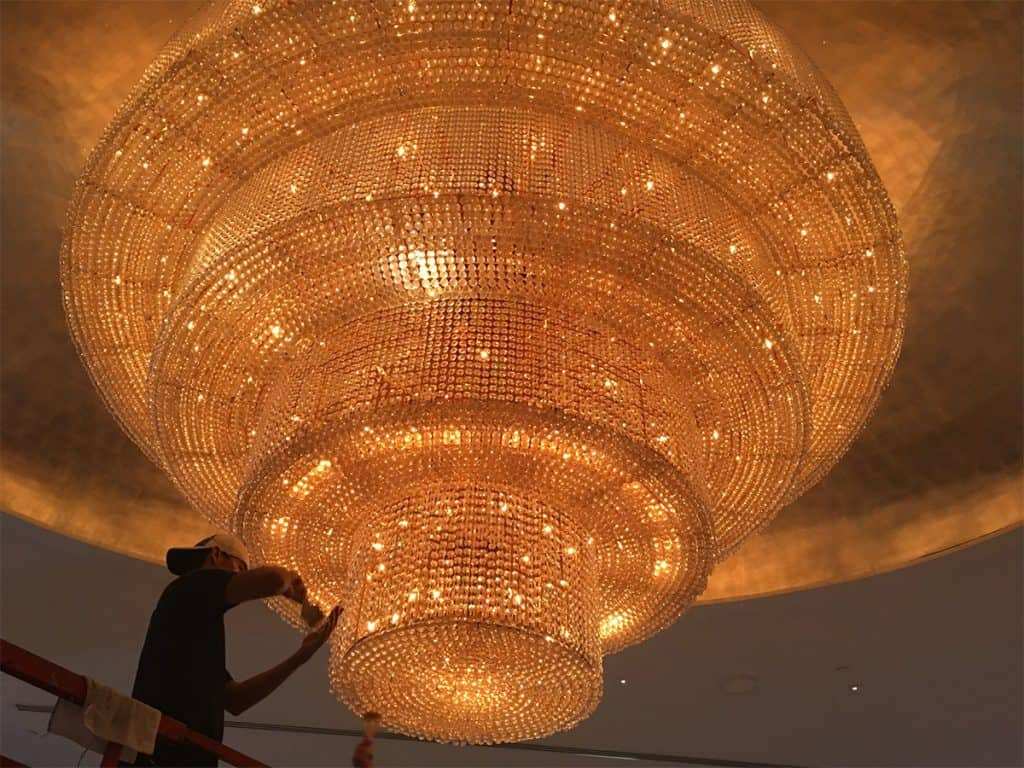 man cleaning a crystal chandelier