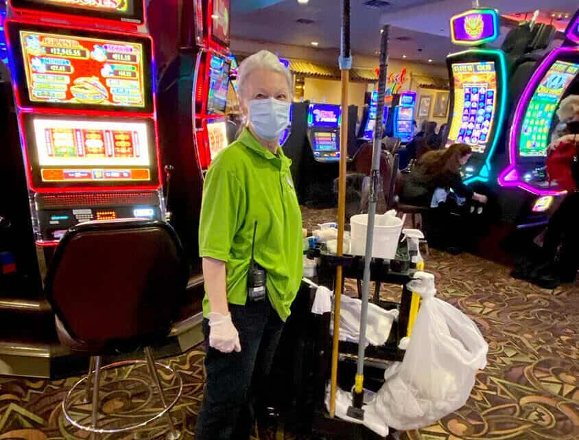 Woman cleaning casino with PPE on