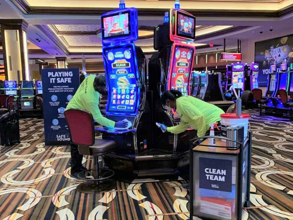 Two employees wearing PPE cleaning and disinfecting casino machines