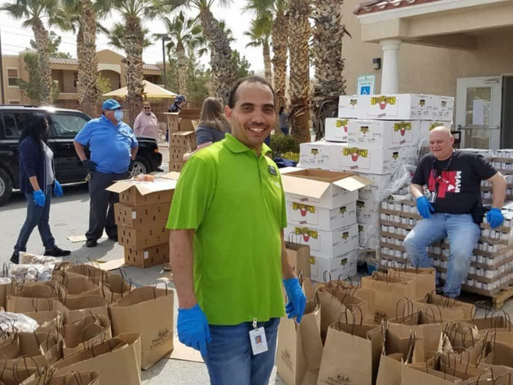 man in green shift working at a covid food drive with cans and boxes behind him