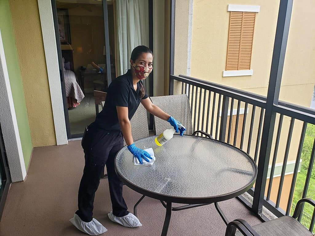 Female employee wearing PPE cleaning table outside